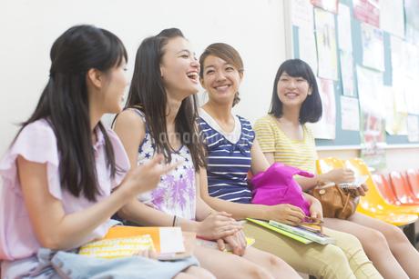 廊下の椅子に並んで座って笑い合う女子学生たちの写真素材 [FYI02967774]