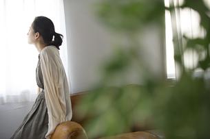 窓際のソファーに寄りかかって遠くを眺める女性の後ろ姿の写真素材 [FYI02967775]