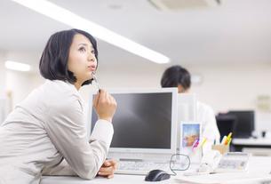 デスクで上を向いて考えるビジネス女性の写真素材 [FYI02967778]