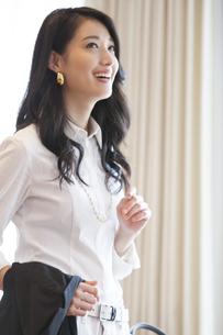 カーテンの傍で微笑む女性のポートレートの写真素材 [FYI02967783]