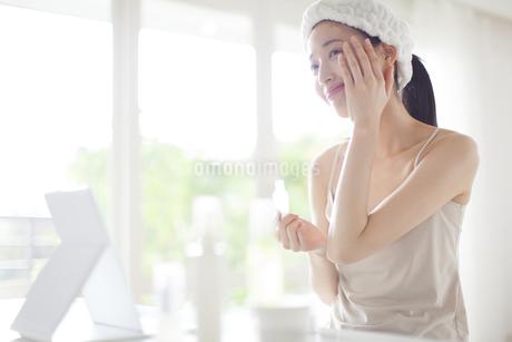 鏡の前でスキンケアをする微笑む女性の写真素材 [FYI02967784]
