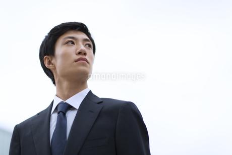 オフィスビルを背景に上を見上げるビジネス男性の写真素材 [FYI02967787]