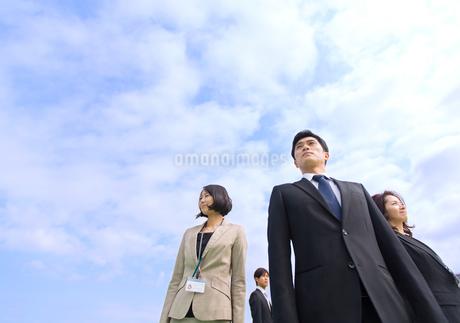 青空を背景に立つビジネス男女の写真素材 [FYI02967790]
