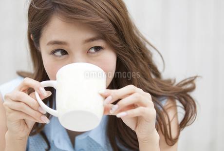 微笑みながら両手でカップを持つ女性の写真素材 [FYI02967791]
