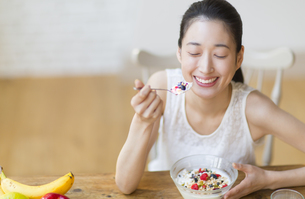 シリアルを食べる笑顔の女性の写真素材 [FYI02967793]
