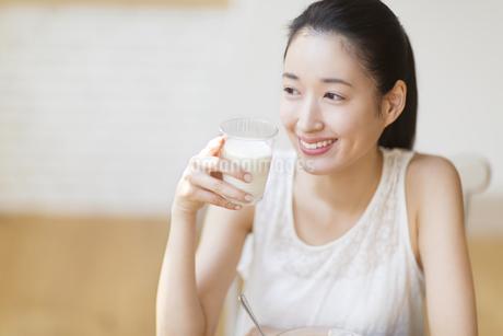 牛乳を手に微笑む女性の写真素材 [FYI02967794]