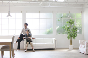ソファーに座って微笑む男性と女性の写真素材 [FYI02967796]
