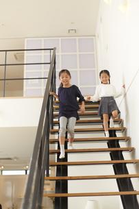 階段を駆け降りる姉妹の写真素材 [FYI02967797]
