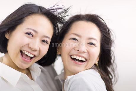 風を受けながら笑う女性2人の写真素材 [FYI02967801]