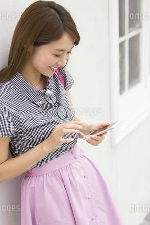 壁に寄り掛かってスマートフォンを操作する女性の写真素材 [FYI02967804]