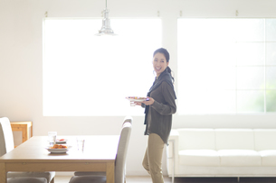 料理を運ぶ笑顔の女性の写真素材 [FYI02967807]