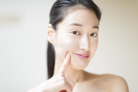 頬に指をあて微笑む女性の写真素材 [FYI02967813]