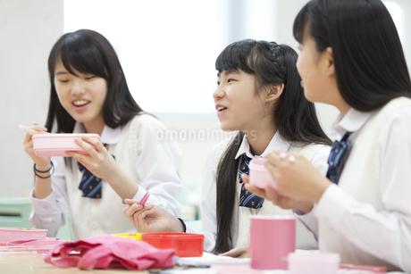 教室でお弁当を食べながら微笑む3人の女子高校生の写真素材 [FYI02967817]