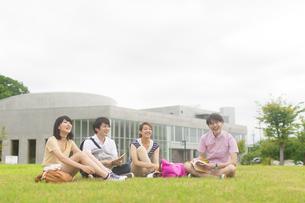 芝に座り遠くをみて微笑む学生たちの写真素材 [FYI02967822]