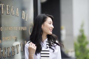 ウィンドウの前で微笑む女性の横顔の写真素材 [FYI02967826]