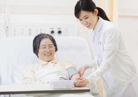 ベッドの患者に血圧計をつける女性看護師の写真素材 [FYI02967835]