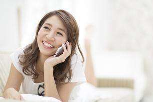 ソファの上で電話をかける女性の写真素材 [FYI02967837]