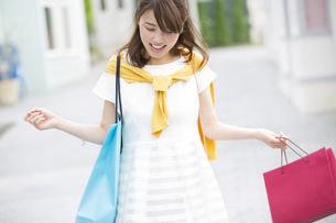 両手でショッピングバッグを持って微笑む女性の写真素材 [FYI02967838]