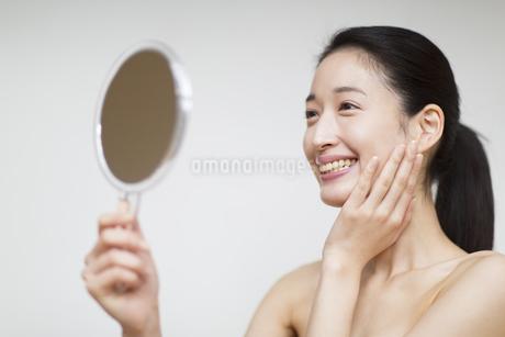 手鏡を見て微笑む女性の写真素材 [FYI02967840]