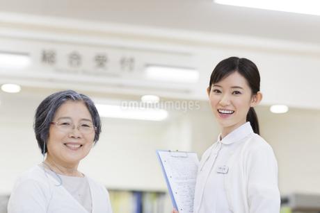 受付前で微笑む患者と女性看護師の写真素材 [FYI02967844]