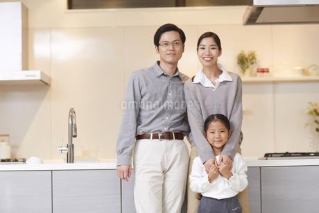 キッチンの前に立つ3人家族の写真素材 [FYI02967846]