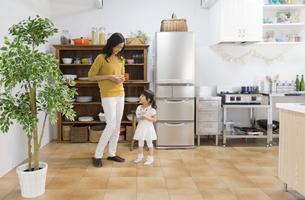 キッチンでカップを手に微笑む親子の写真素材 [FYI02967852]