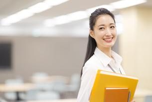 オフィスでファイルを手に微笑むビジネス女性の写真素材 [FYI02967853]