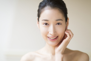 頬に片手を添えて微笑む女性の写真素材 [FYI02967859]