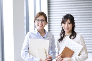 オフィスビルのロビーで立つ2人のビジネス女性の写真素材 [FYI02967861]
