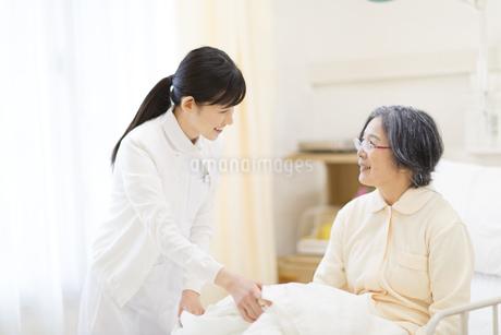 ベッドの患者と話をする女性看護師の写真素材 [FYI02967862]