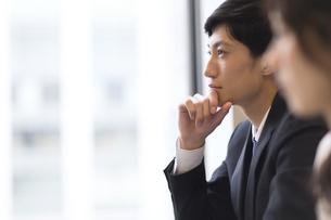 顎に手をあて考えるビジネス男性の横顔の写真素材 [FYI02967863]