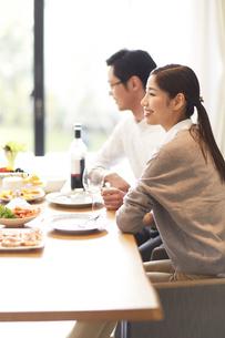 ワインと食事を前に男性と一緒に微笑む女性の写真素材 [FYI02967865]