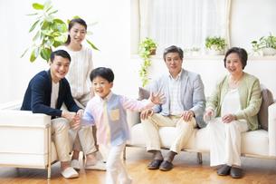 走る子供を見て笑う家族の写真素材 [FYI02967868]