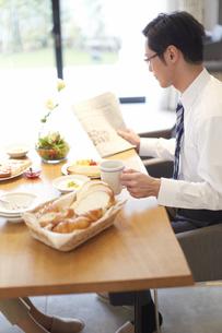 出勤前に新聞を手に朝食をとる男性の写真素材 [FYI02967870]