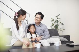 ソファーでくつろぐ3人家族の写真素材 [FYI02967874]