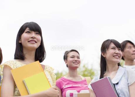 ノートを胸にあて遠くをみる学生たちの写真素材 [FYI02967877]