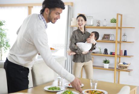 ダイニングで食事の準備をする男性と赤ちゃんを抱えて微笑む女性の写真素材 [FYI02967878]