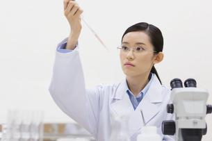 ピペットを使って計量している女性研究員の写真素材 [FYI02967879]