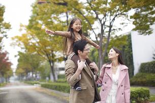 肩車して遊歩道を歩く家族の写真素材 [FYI02967880]