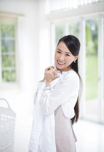 洗濯物を抱いて微笑む奥さんの写真素材 [FYI02967881]