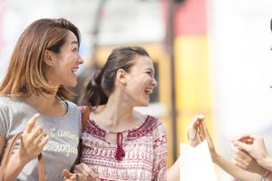 買物中に人と手を合わせる2人の女性の写真素材 [FYI02967882]