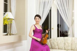ドレスアップしてバイオリンを持つ笑顔の女性の写真素材 [FYI02967885]