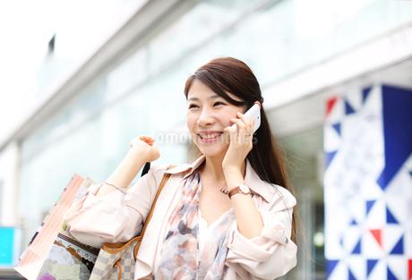 スマートフォンで会話する買物中の女性の写真素材 [FYI02967891]