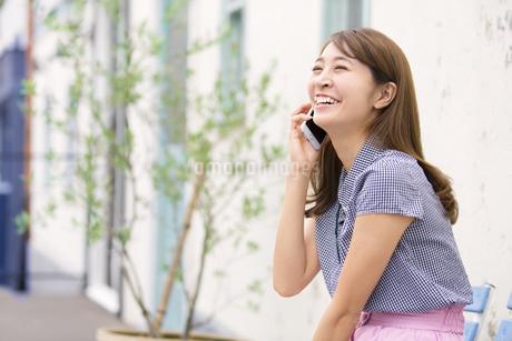 ベンチに座って電話をかける女性の写真素材 [FYI02967893]