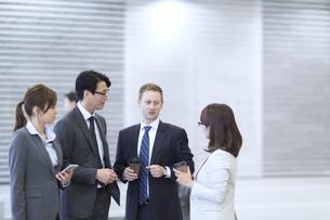 オフィスビルのロビーで立って会話するビジネス男女の写真素材 [FYI02967894]