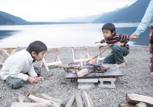 湖畔でおこした焚火を囲む子供たちの写真素材 [FYI02967896]