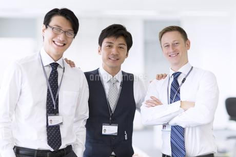 肩に手をかけて微笑むビジネス男性3人の写真素材 [FYI02967897]