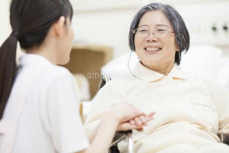 車椅子の患者の手に手を添える女性看護師の写真素材 [FYI02967898]