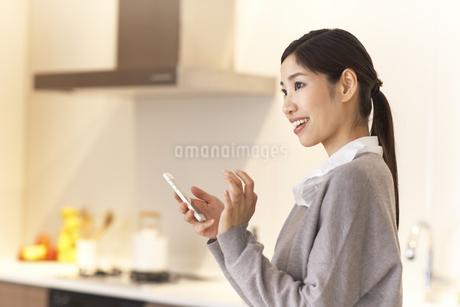 キッチンでスマートフォンを手に遠くをみる女性の写真素材 [FYI02967903]
