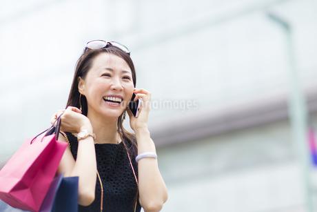 スマートフォンで会話する買物中の女性の写真素材 [FYI02967905]